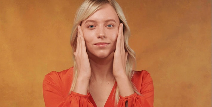woman applying cream on an orange background