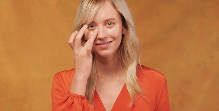 woman applying eye cream on an orange background